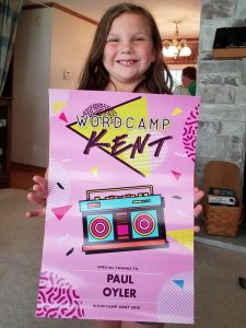 My beautiful granddaughter holding the incredible poster, designed by Sarah Yoder, that was the speaker gift at WordCamp Kent.