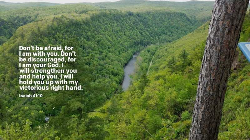 """Photo of a river thru a wilderness canyon, with Bible verse superimposed upon it of Isaiah 41:10 - """"Don't be afraid, for I am with you. Don't be discouraged, for I am your God. I will strengthen you and help you. I will hold you up with my victorious right hand."""""""
