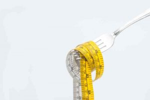 Photo of a measuring tape wrapped around a fork, used for illustrating my weight loss update.
