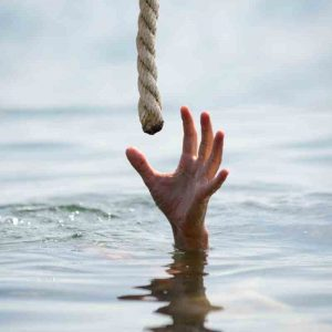 Photo of a hand reaching up out of a body of water for a lifeline.