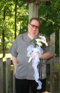 Photo of me with a goofy grin, holding the flowers while Debbie ran home to get her vows.