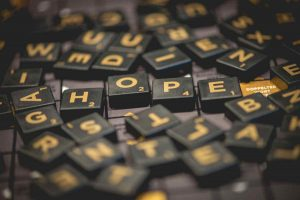 Random photo of letter tiles with the word 'hope' in the center of the pile.